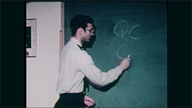 1980s: Man stands at chalkboard, writes on board. People sit at table, watch man. Wright-Patterson Air Force Base. Men sit at table, write.