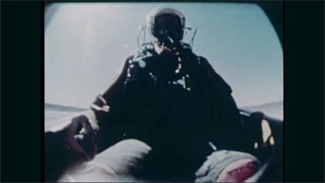 1980s: Plane flies low over desert, drops packages. Men stand by jeep, watch plane. Test dummy ejects from cockpit.