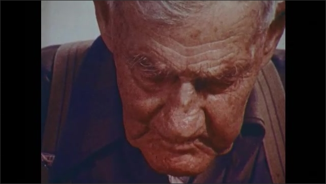 1970s: UNITED STATES: man eats bread at table. Man puts spoon in mouth. Man chews food. Close up of old man's face. Man eats meal at table