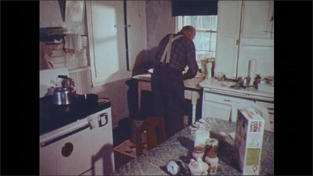 1970s: UNITED STATES: close up of hands washing cutlery in sink. Man washing up at sink. Man in kitchen from behind. Glasses on table. Hand picks up glasses.