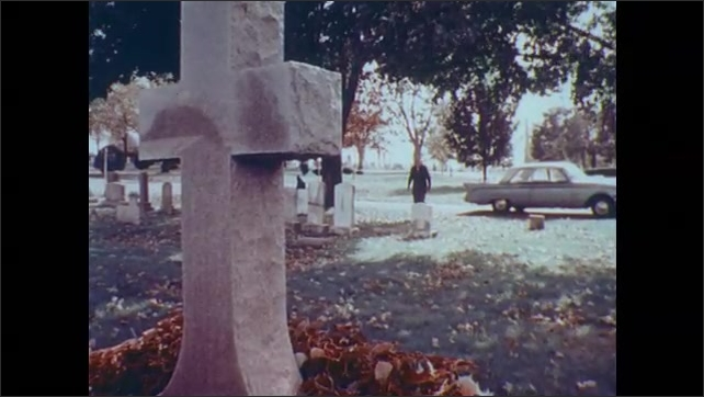 1970s: UNITED STATES: car arrives at cemetary. Man gets out from car. Man walks to grave