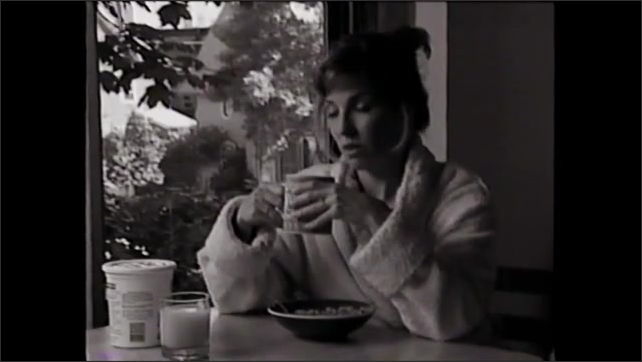 1990s: woman tosses and turns in bed, woman in bathrobe looks sad at breakfast while poking at bowl of food, picks up coffee mug, shakes head, woman peeks through window blinds, closes blinds