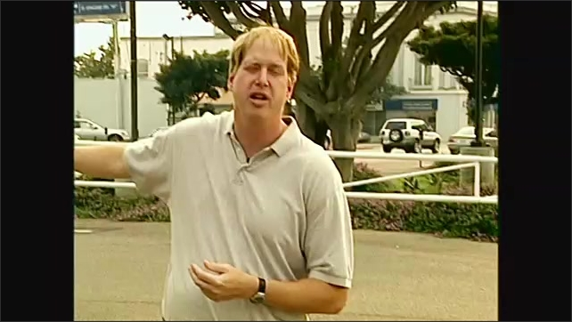 2000s: landscaping in parking lot, man talking about runoff in parking lot, people walking on sidewalk, person picking up trash on beach