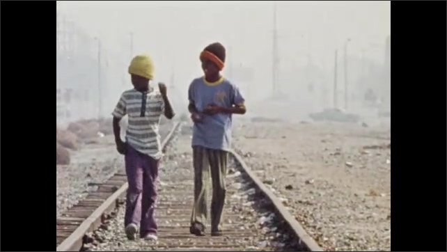 1970s: UNITED STATES: children walk along railway tracks.
