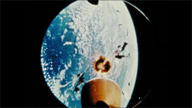 1970s: UNITED STATES: slow motion of rocket in space. Debris from rocket. Children in classroom.