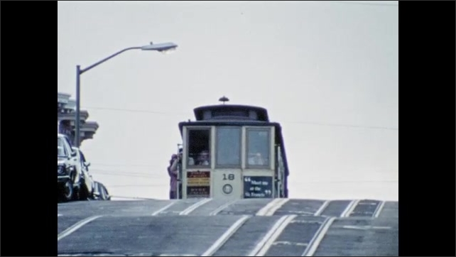 1970s: UNITED STATES: people ride bicycles. Trolley appears over hill.