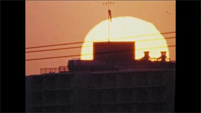 1970s: UNITED STATES: sun sets behind city building. Lights on cars early in morning.