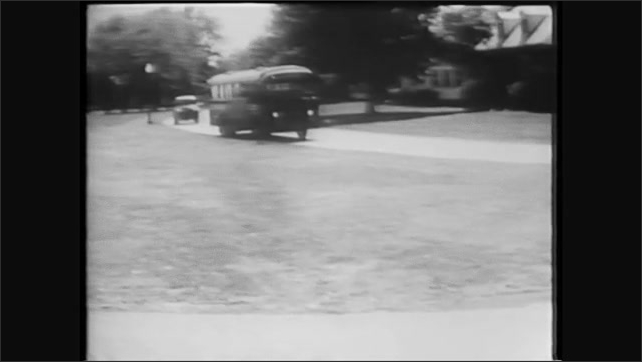 1960s: Truck drives down the street. Bus drives down the street, stops at stop sign.