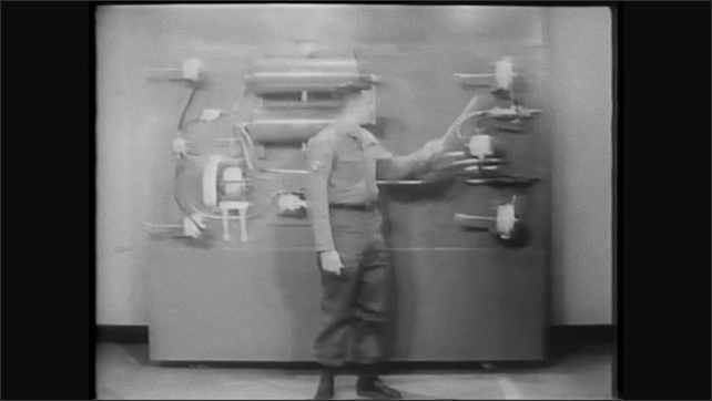 1960s: Man stands next to air brake system display, points at components.