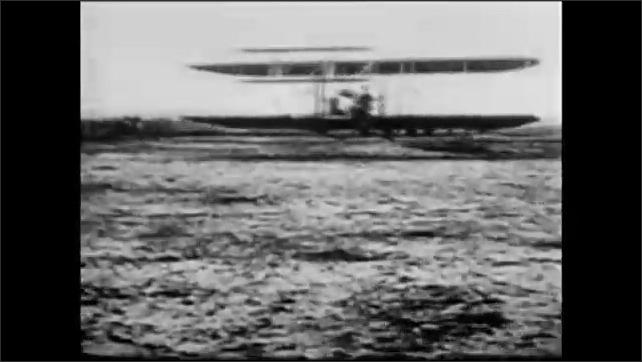 1960s: Men spin propellers on airplane.  Plane flies.