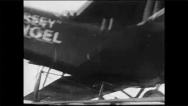 "1960s: People celebrate in street.  Headline reads ""GERMANY SURRENDERS.""  Parade.  Men perform stunts in air.  Man sits on top of plane as it lands."