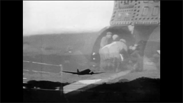 1960s: Pilots in cockpit.  Shipyard.  Men load cargo into hold.  Airplane takes off.  Submarine surfaces.