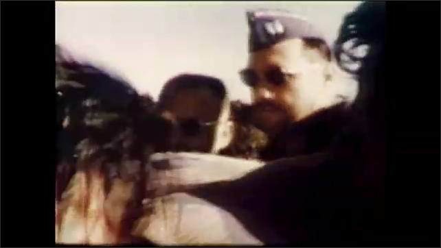 1960s: People get off helicopter.  Man carries injured woman.  Soldiers tend to people