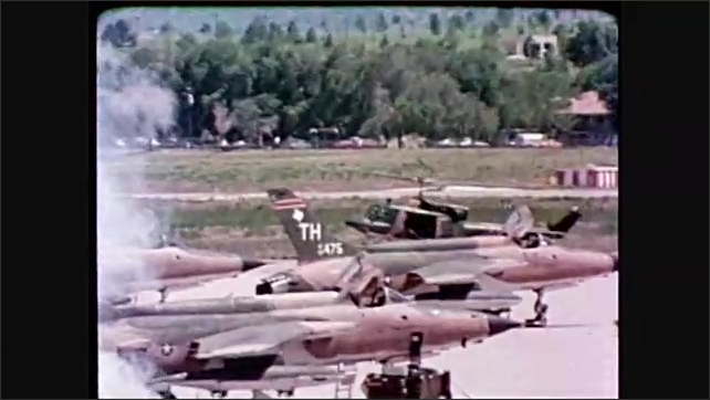 1980s: F-16 Fighter jet flies over runway. Soldiers scramble and prepare jets for take off. Helicopter flies low over runway. Soldiers leap of helicopter and fire guns and smoke canisters.