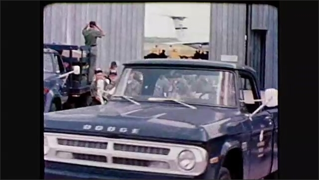 1980s: Soldier salutes car at entry checkpoint. Soldiers enter hangar and distribute paperwork and clothing. Soldiers disembark from cargo plane. Soldiers adjust parachute back packs in field.