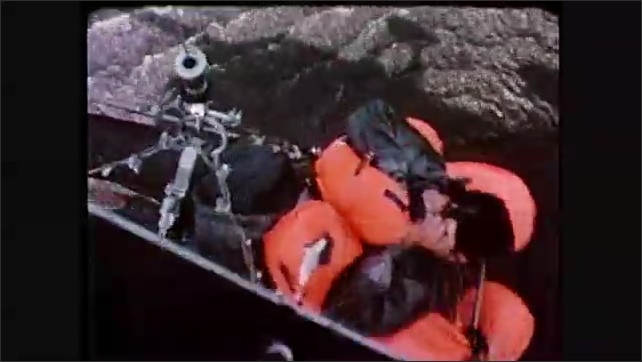 1980s: Helicopter lifts man in rescue gurney from lake.  Helicopter hovers over lake