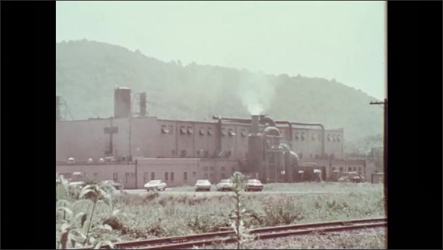 1970s: Smokestack belches thick white smoke into air. Industrial plant releases smoke from stacks. Smokestack belches thick white smoke into air.