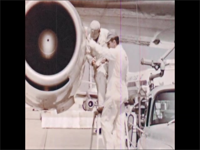 1960s: Passengers board airplane. Worker refuels plane. Workers check engine of airplane. Man loads luggage onto cart. Cart drives luggage to plane.