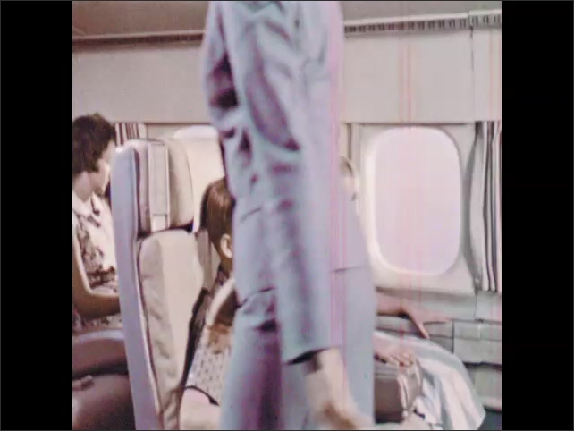 1960s: Passengers eat lunch at seats in airplane. Airplane flies above clouds. Stewardess speaks to children in plane. Boy and girl recline seats. Stewardess hands passenger a pillow.