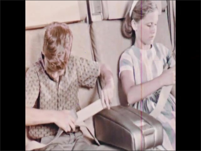 1960s: Airplane wing and engines outside window. Children fasten seatbelts. Plane flies over San Francisco, California.
