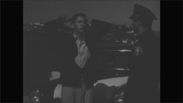 1950s: Officer gives boy a drunk driving test. Boy wavers and stumbles backwards. Boy and officer point. Face of officer.