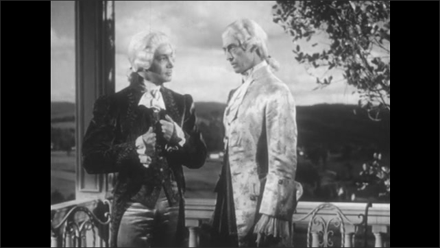 1950s: Two men talk on a terrace and wear Victorian clothing, man on the left talks, holds the other man's arm and gesticulates while he talks, the other man shakes his head.