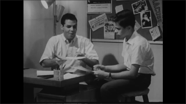 1940s: Man sits in front of console pressing buttons and turning knobs. Man sits at desk talking to boy sitting next to him. Man talks. Boy talks.