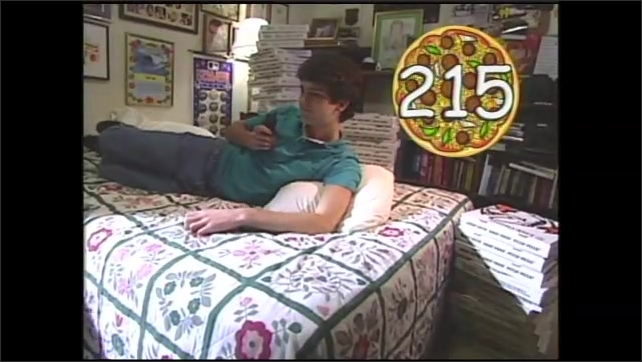 1990s: Bedroom, boy lies on bed, talks on phone, looks annoyed, mom walks in, places stacks of pizza boxes on floor, bed. Boy looks confused, protests.