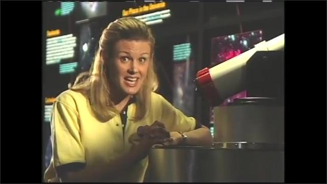 1990s: Science museum, girl leans on telescope, talks, points, gestures, raises eyebrows, shoulders, looks into telescope.