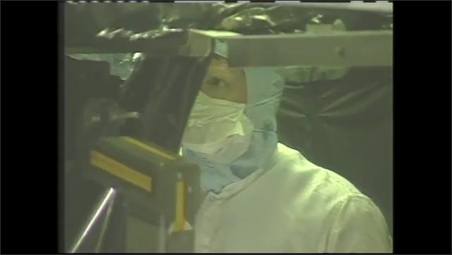 1990s: Woman talks, gestures, explains. Clean room, man in hazmat suit inspects instruments, holds light bulb.