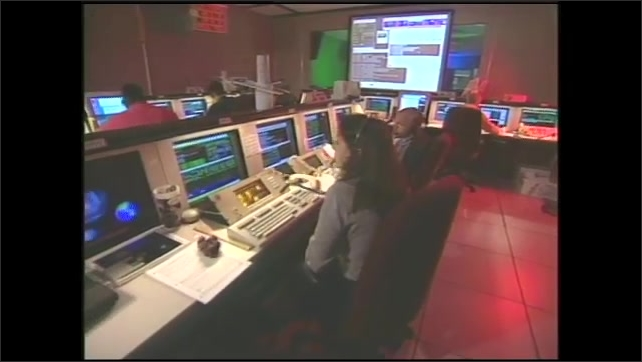 1990s: NASA data collection control room, computers, men, women work, wear headsets.