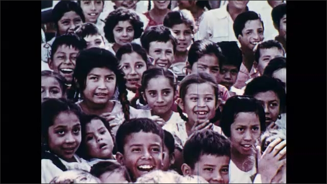 1960s: Two men smile, speak in crowd. Crowd of children smile. Young girl smiles below man with pipe in his mouth and child on his back, boy smiles.