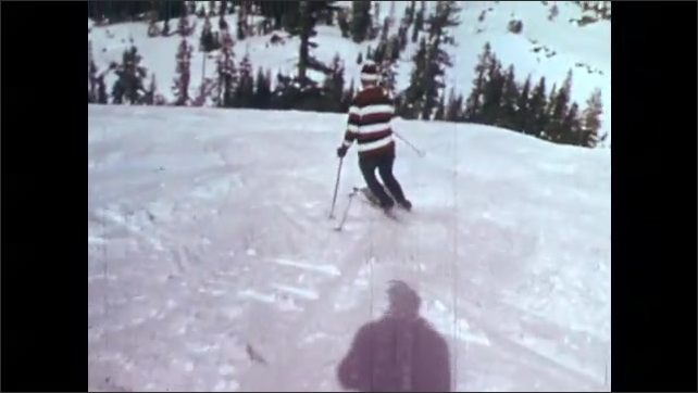 1970s: two men standing talking to each other on ski slopes, people skiing down slopes