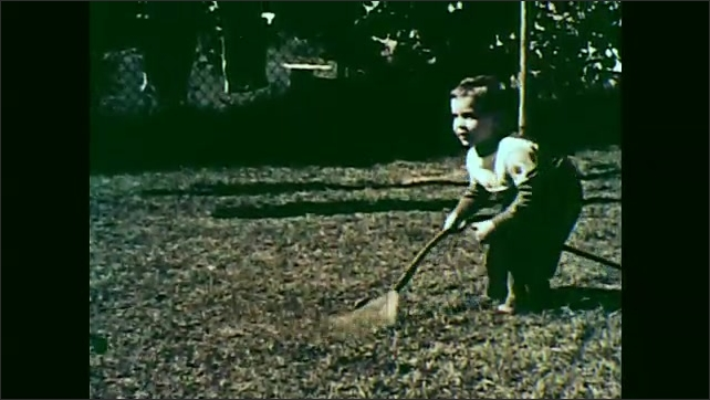 1950s: boy in sweater turns outdoor faucet, runs across yard, picks up garden hose, sprays water in the air and smiles. woman looks out window. shoes stand in wet grass.