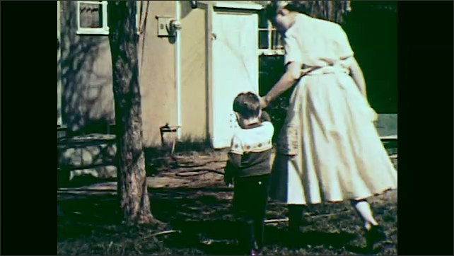 1950s:  woman grabs garden hose, takes hand of boy, walks across the backyard and  turns off the outdoor faucet on house.