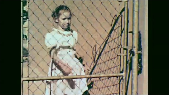 1950s: girl dries foot and fights for towel with boy in sweater on lounge chair. girl opens gate on fence next to house and talks to girl in red dress at backyard of house.