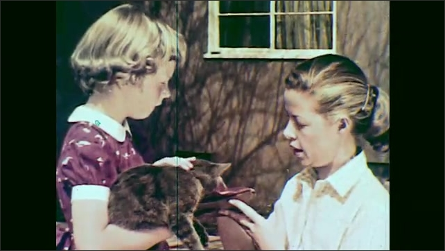 1950s: girl in red dress holds and pets Russian Blue cat, listens to woman in apron, takes a pair of shoes and straightens socks on boy in sweater in backyard.