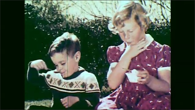 1950s: girl in red dress and boy in sweater smile and eat ice cream out of bowls while sitting on lawn in backyard.
