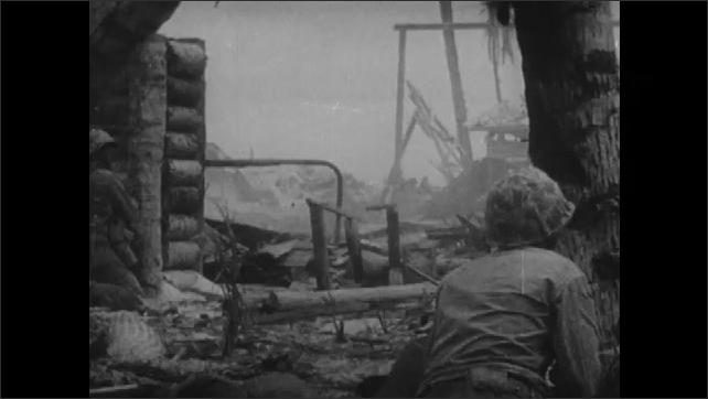 1940s: Smoke and fire rises from bombed pill box. Soldiers crawl and hide behind debris as they approach enemy fortification. Soldiers hide behind wall and reload guns.