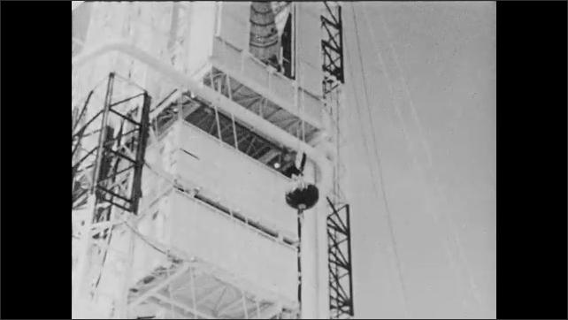 1960s: UNITED STATES: rocket in gantry. Crane moves satellite onto spring.