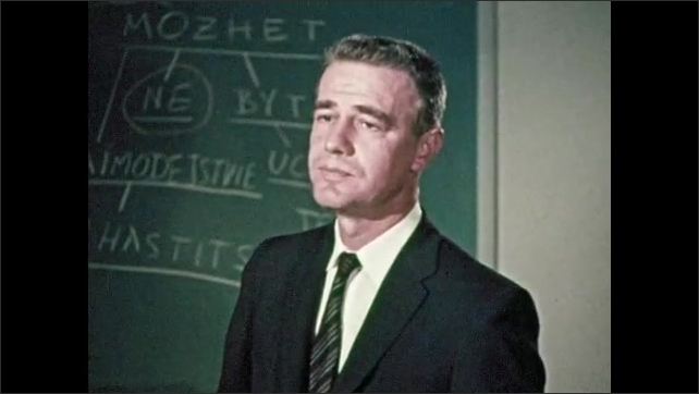 1950s: Lights on electronic machinery flash, paper runs through printer, man stands in front of chalkboard. People stand around woman seated at desk, talk, look at papers.
