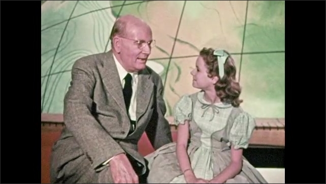 1950s: Man and girl sit down, talk.