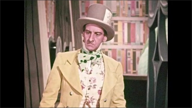 1950s: Man in top hat and costume talks excitedly, raises eyebrows, stares angrily. Young girl looks concerned, talks. Professor talks. Costumed man raises hand, gives sarcastic look.