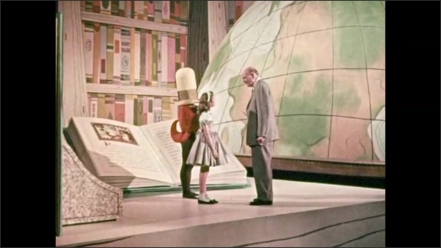 1950s: Person wears tap dancing costume and huge hat hiding face, stands by bookshelf, large book. Girl walks away, professor touches her arm, talks, she turns around, listens. Man points to globe.