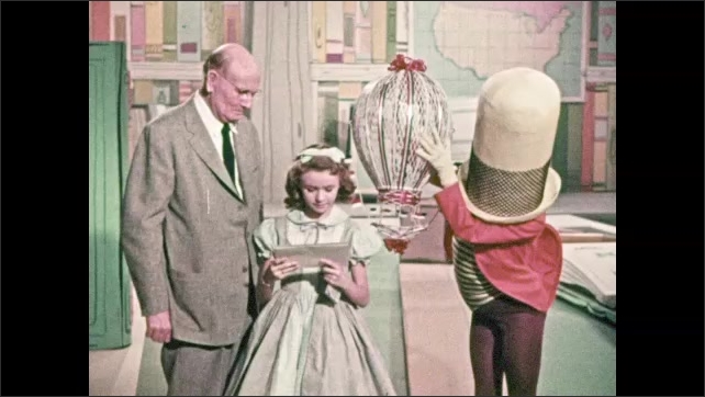 1950s: Young girl runs across room, hot air balloon descends carrying envelope. Person wears tap dancing costume and hat obscuring face. Girl talks to Professor, opens invitation, looks excited.