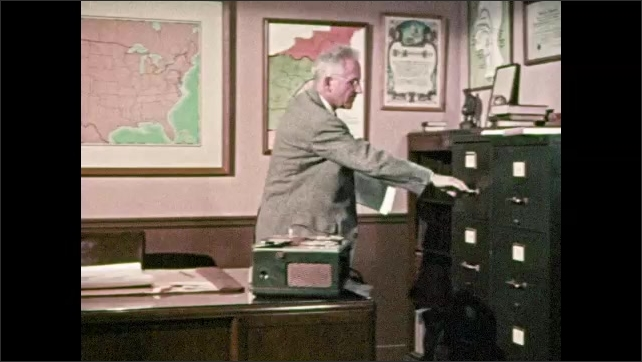 1950s: Man points to sign for the Linguistic Atlas of the United States. Man sits at desk, turns pages, writes, stands up, files papers, takes new papers out of drawer, sits back down at desk.