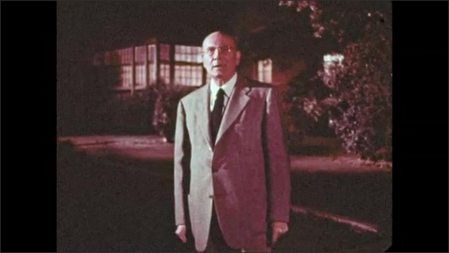 """1950s: Man stops in front of house and gestures at entrance. Title  """"The Alphabet Conspiracy"""" appears."""