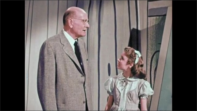 1950s: Cartoon man puts away quill and paper and picks up reed from bagpipe. Man walks by with building materials in his arms. Man speaks to girl. Man opens his mouth.