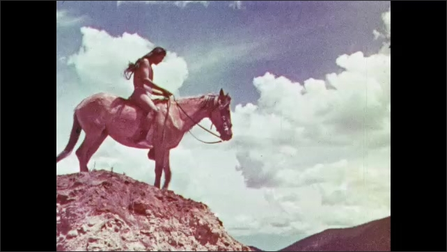 1950s: Man in tall hat cranks film reel. Man in suit speaks. Indigenous villagers. Native American on horseback. Native American makes hand signals. Native American tepees.