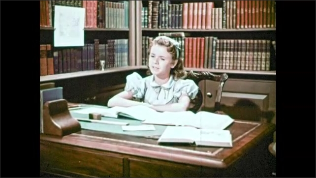 1950s: Small girl sits at large desk in a study. Girl is studying and looks frustrated. Girl slams book closed and places head on desk.